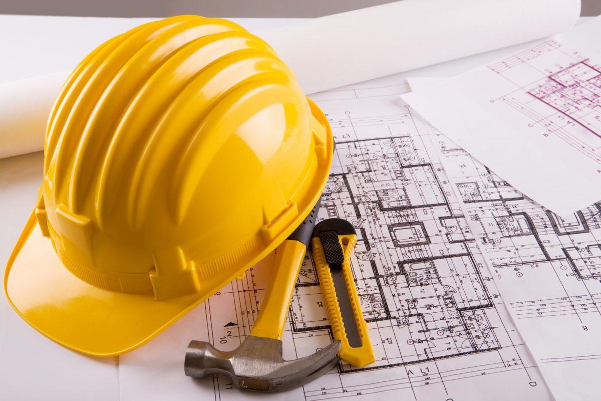 construction hat on house plan blueprints