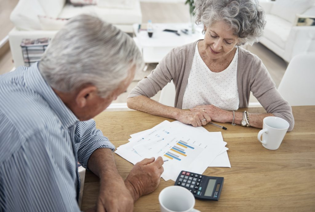old couple talking over financial charts